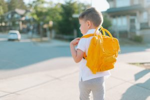 Small blond little boy with a yellow backpack School Refusal